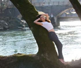 Woman leaning on a tree by the river Stock Photo