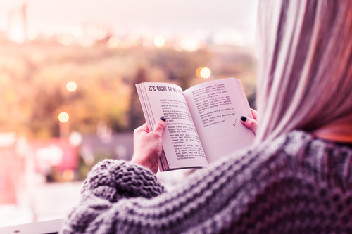 Young Woman Reading a Book on Terrace Stock Photo
