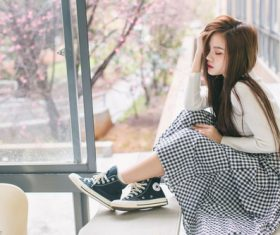 Asian girl sitting at the window with her eyes closed Stock Photo