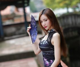 Asian girl wearing cheongsam holding fan Stock Photo