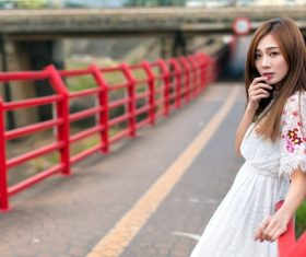 Asian woman in white dress leans on the road railing to take photo Stock Photo