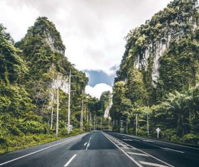 Asphalt road with mountains on both sides Stock Photo