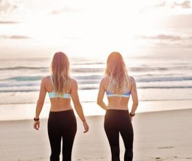 Back view of two women walking on the beach Stock Photo