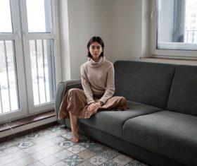 Barefoot woman sitting on sofa indoors Stock Photo