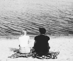 Black and white photography couple sitting on the beach Stock Photo