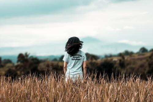 Child standing in the dry grass Stock Photo