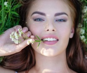 Closeup of beautiful woman lying on the grass Stock Photo