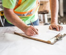 Construction worker writing on notepad Stock Photo
