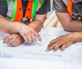 Construction workers discussing design drawings Stock Photo