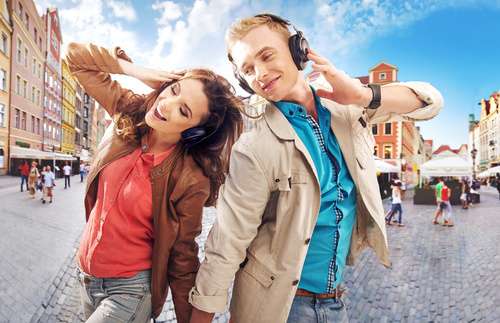 Couples wearing headphones to listen to music in the city square Stock Photo 02