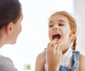 Doctor doing oral examination for little girl Stock Photo