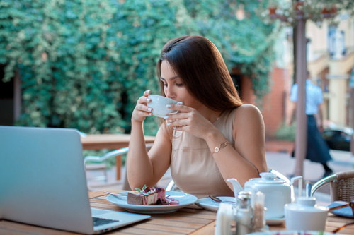 Girl drinking coffee in outdoor cafe Stock Photo