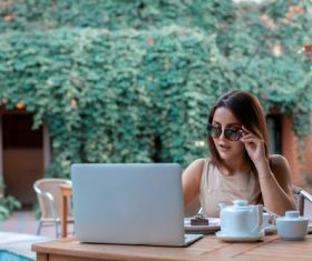 Girl wearing sunglasses in an outdoor cafe surfing the internet Stock Photo