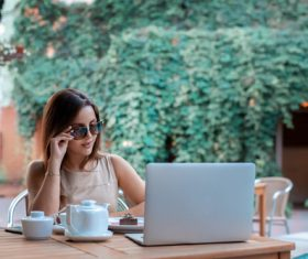 Girl wearing sunglasses in outdoor cafe Stock Photo
