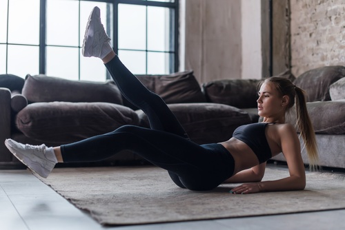 Indoors working out legs up women Stock Photo