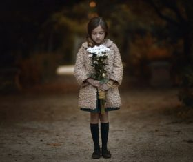 Little girl looking down at the bouquet in hand Stock Photo