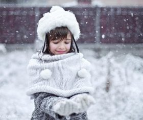 Little girl playing snow outdoors on snowy day Stock Photo