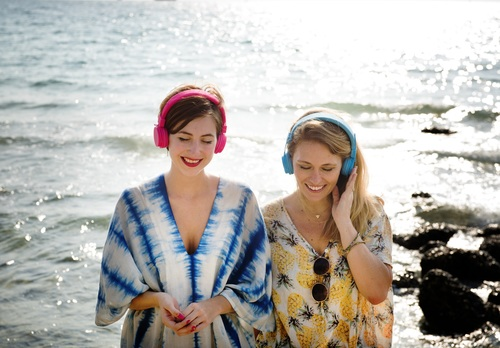 Mother and daughter with headphones at the seaside Stock Photo