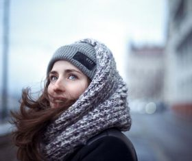 Outdoor blue eyes woman wearing knitted hat around scarf Stock Photo