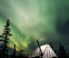 Outdoor night bright tents and Northern Lights Stock Photo