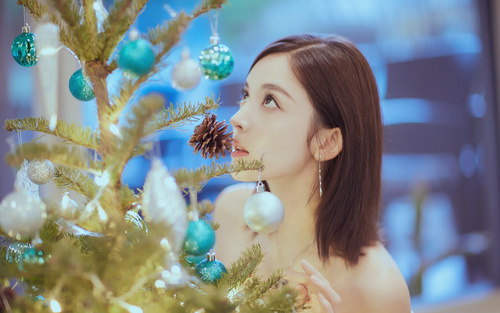 Pretty asian girl looking at christmas tree Stock Photo 01