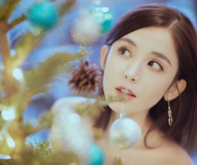 Pretty asian girl looking at christmas tree Stock Photo 02