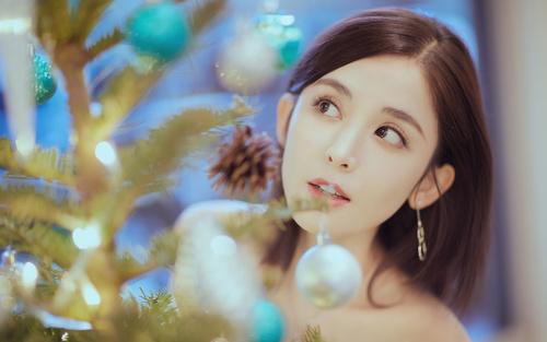 Pretty asian girl looking at christmas tree Stock Photo 02