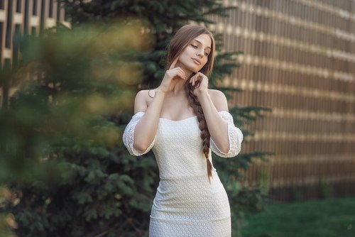Pretty girl in white dress standing outdoors posing Stock Photo