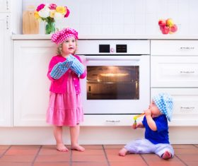 Sister and brother playing in the kitchen Stock Photo 04