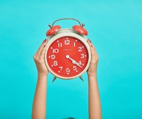 Small alarm clock in woman hands Stock Photo