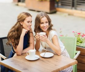 Stock Photo Woman chatting at outdoor cafe drinking coffee