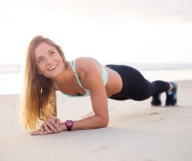 Stock Photo Woman doing push-ups on the beach