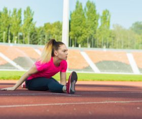 Stock Photo Woman doing stretching exercise on the stadium