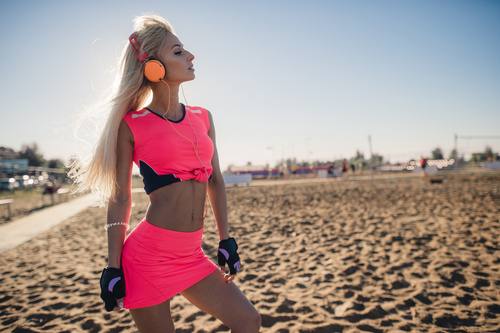 Stock Photo Woman in pink is listening to music with headphones