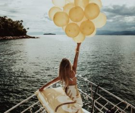 Stock Photo Woman standing on the yacht holding up balloons