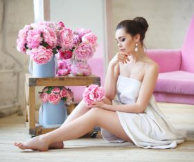 Stock Photo Woman wearing bath towel sitting on the floor holding flowers