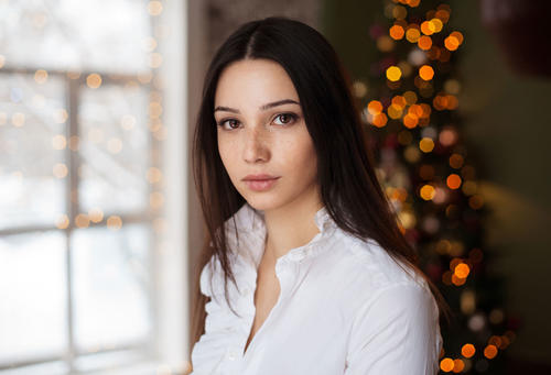 Stock Photo Young girl with christmas tree behind