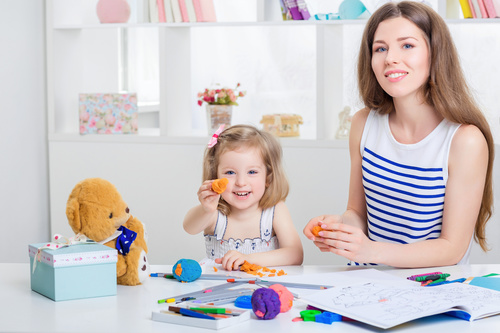 Stock Photo Young mom and daughter holding plasticine