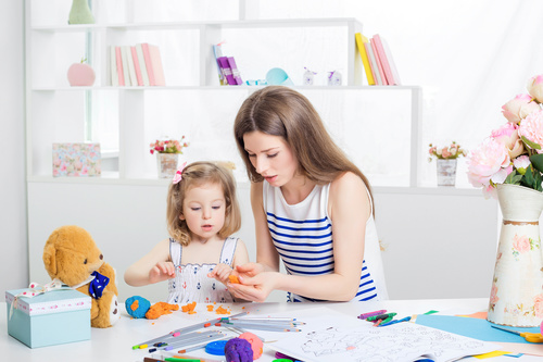 Stock Photo Young mother licks animal with plasticine