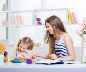 Stock Photo Young mother teasing daughter laughing