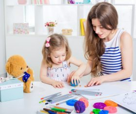 Stock Photo Young mother with her daughter playing with plasticine
