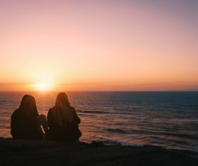 Two women sitting on the beach watching the sunrise Stock Photo