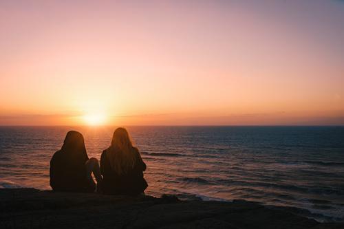 Two women sitting on the beach watching the sunrise Stock Photo