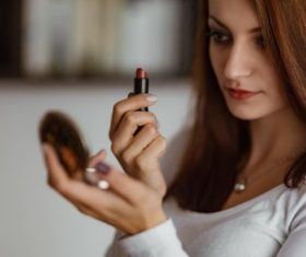 Woman holding small mirror and lipstick Stock Photo