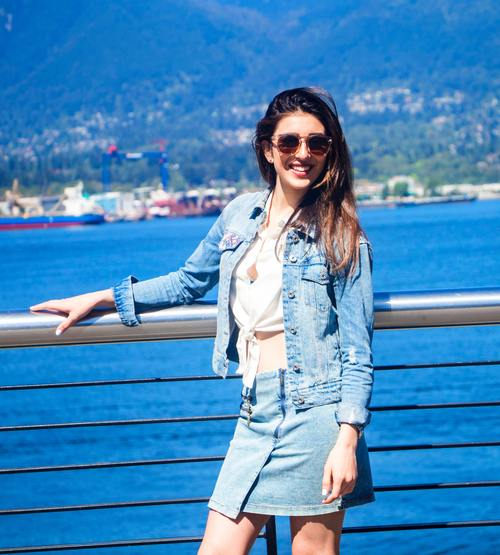 Woman in denim takes a picture on the bridge with sunglasses Stock Photo