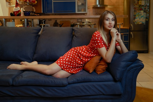 Woman in red dress indoor lying on sofa Stock Photo