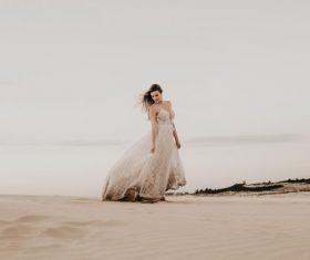 Woman in white dress walks on the beach Stock Photo