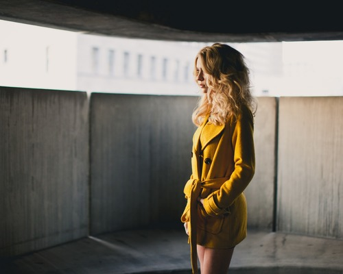Woman in yellow coat looks into the distance Stock Photo