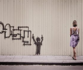 Woman looking at graffiti on the wall Stock Photo