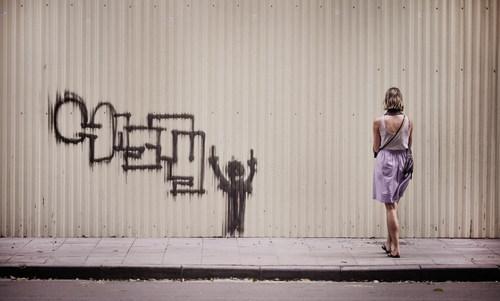 Woman looking at graffiti on the wall Stock Photo